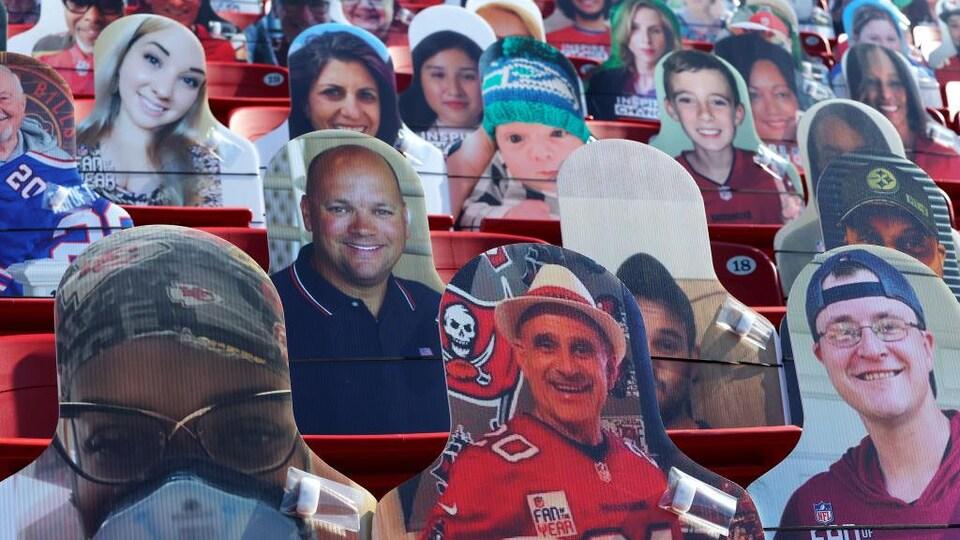 Des cartons illustrant différentes personnes sont installés sur les sièges dans le stade.