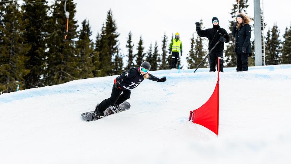 Une femme dévale une pente sur sa planche à neige.