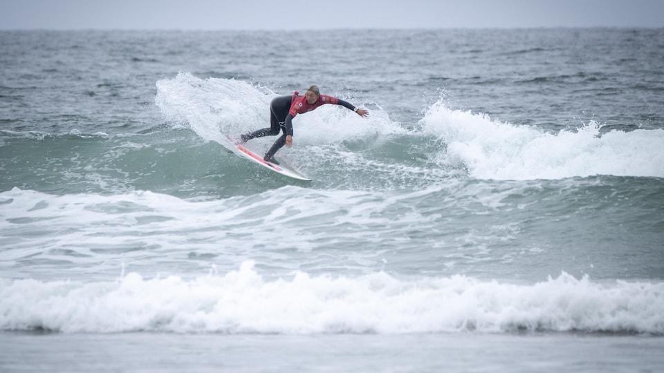 Une jeune femme surfe une vague en effectuant un virage.