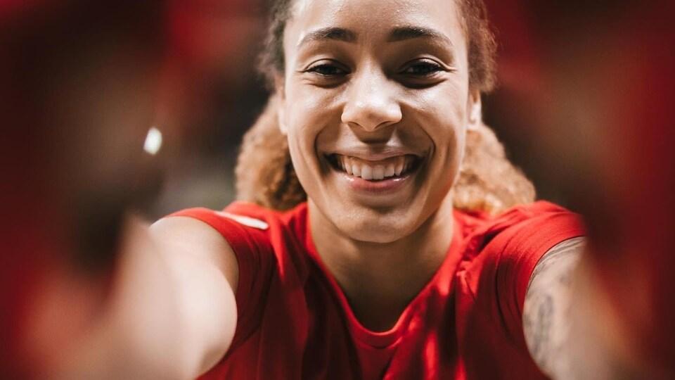 La boxeuse, vêtue d'un t-shirt rouge avec une feuille d'érable et des lauriers blancs, esquisse un large sourire et semble tenir la caméra à bout de bras.