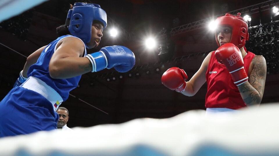 Tammara Thibeault (rouge) regarde son adversaire avec les poings levés