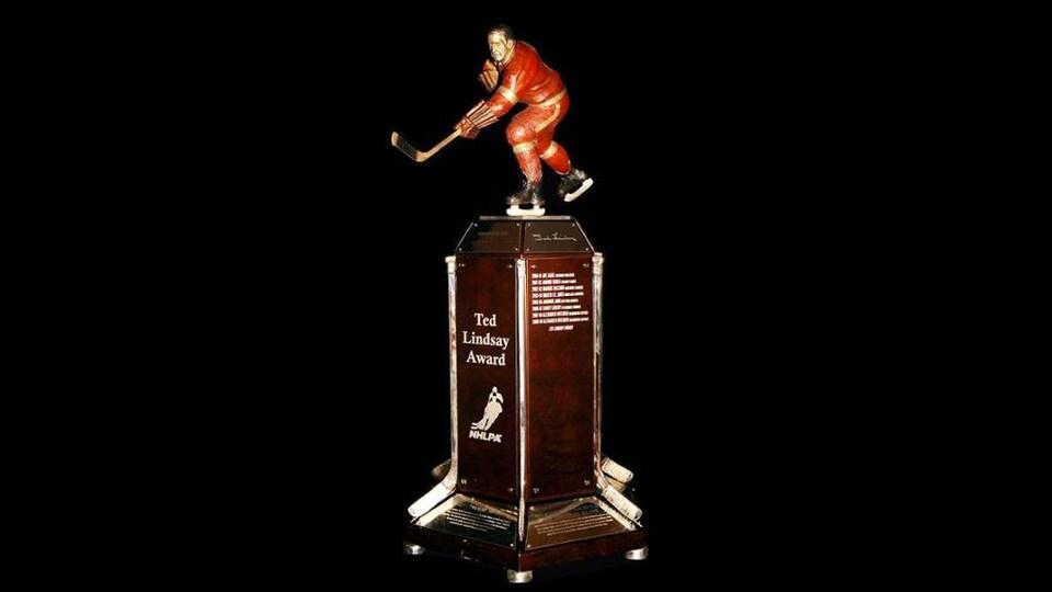 Un trophée montrant un socle rectangulaire debout surmonté d'une statuette d'un joueur de hockey.