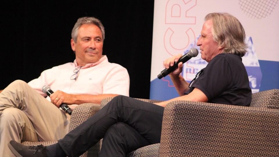 Deux hommes assis en point de presse.