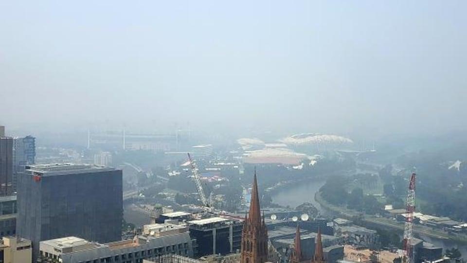 La fumée enveloppe Melbourne et le stade Rod Laver.