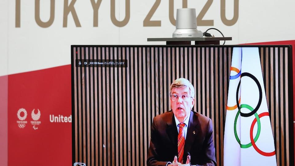 Il apparaît à l'écran d'un moniteur superposé au logo Tokyo 2020.