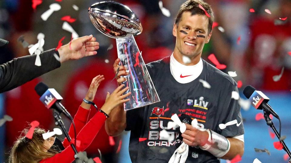 Un homme sur un podium tient un trophée dans ses mains.