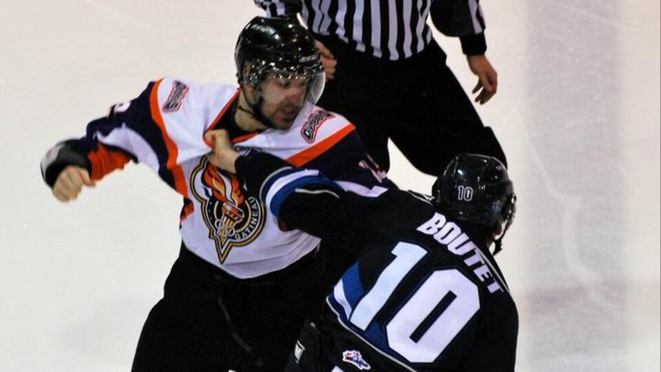 Deux joueurs se bagarrent pendant un match de hockey.