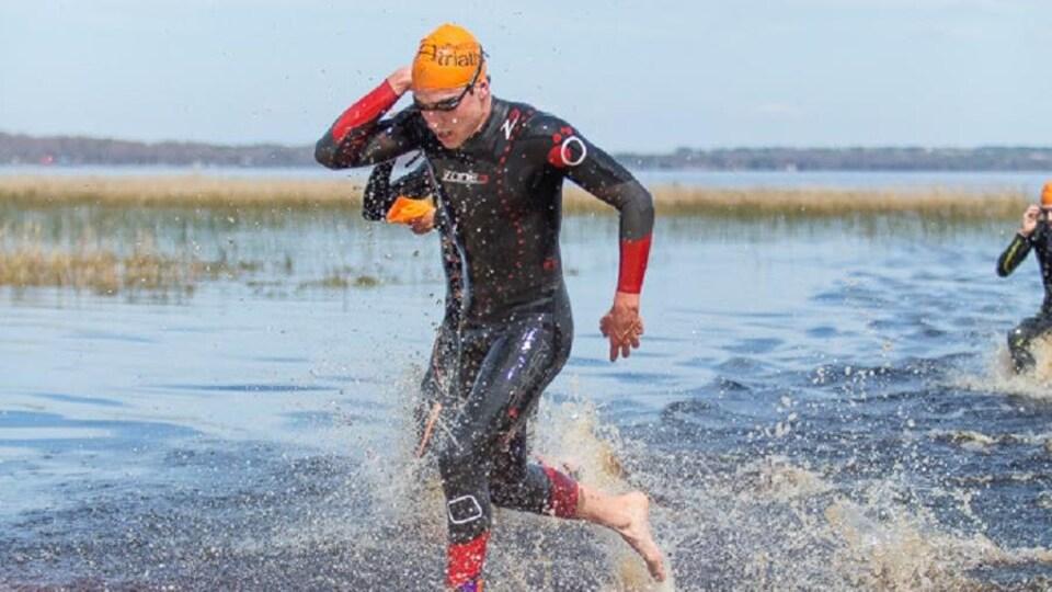 Le triathlonien en habit de nage est debout dans l'eau.