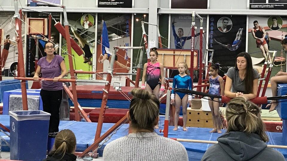 Une entraîneuse parle à des jeunes dans un cours de gymnastique.
