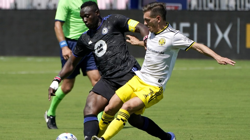 Deux joueurs de soccer se disputent le ballon en milieu de terrain.