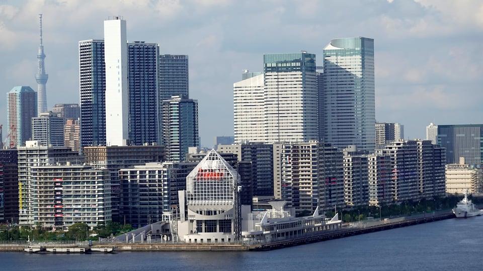 De nombreux bâtiments, dont quelques gratte-ciel, se trouvent au bord d'une étendue d'eau.