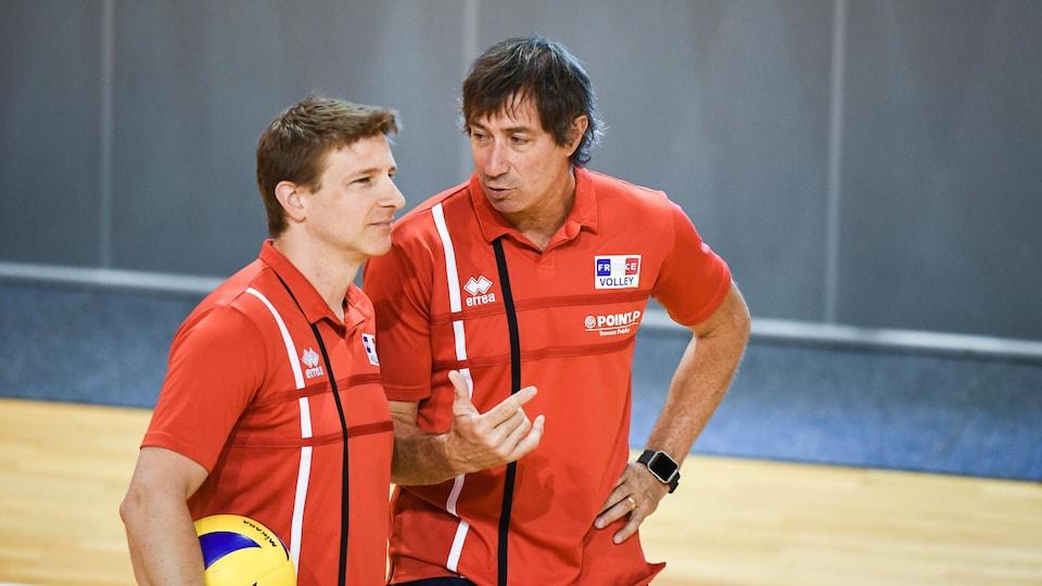 Deux entraîneurs de volleyball aux chandails rouges de l'équipe de France discutent pendant un entraînement.