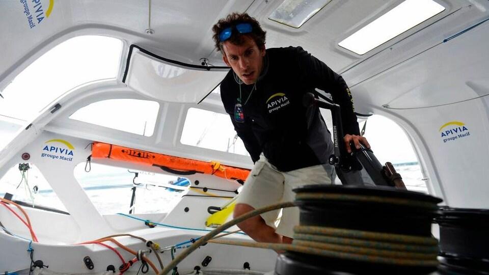 À bord de son voilier, il porte attention aux ajustements à apporter.