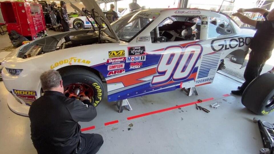 Des mécaniciens travaillent sur la voiture no 90 d'Alex Labbé dans un garage.