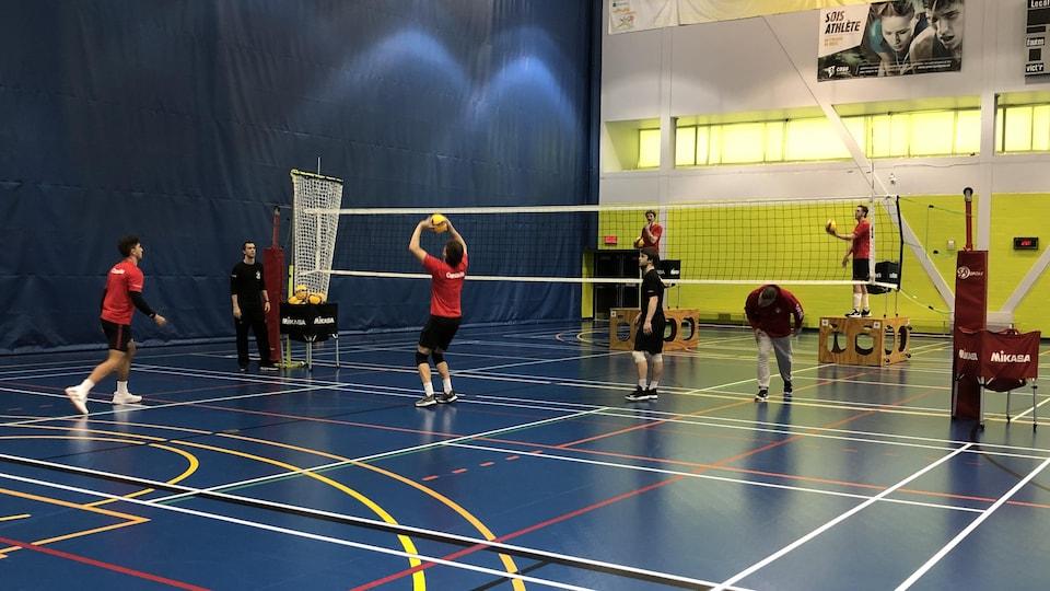 Des joueurs de volleyball frappent le ballon pendant un entraînement.