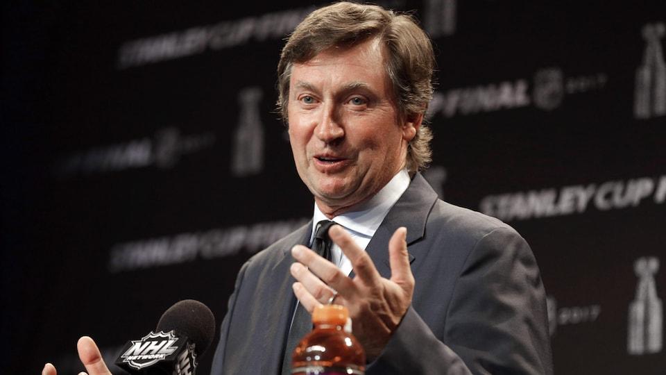 Wayne Gretzky devant un lutrin en conférence de presse répond à des questions.