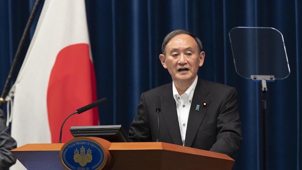L'homme se tient debout devant un drapeau du Japon