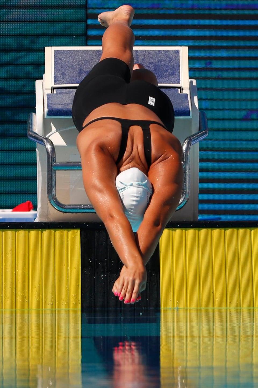 Une nageuse plonge pour commencer une course.