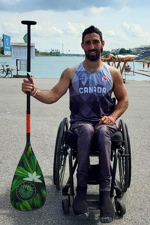 Il prend la pose dans son fauteuil roulant avec sa pagaie.