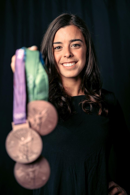 Meaghan Benfeito montre ses trois médailles de bronze olympiques en souriant.