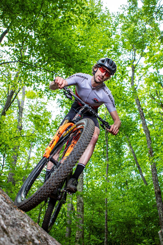 Un cycliste vêtu de blanc et de gris roule sur une roche en vélo de montagne.