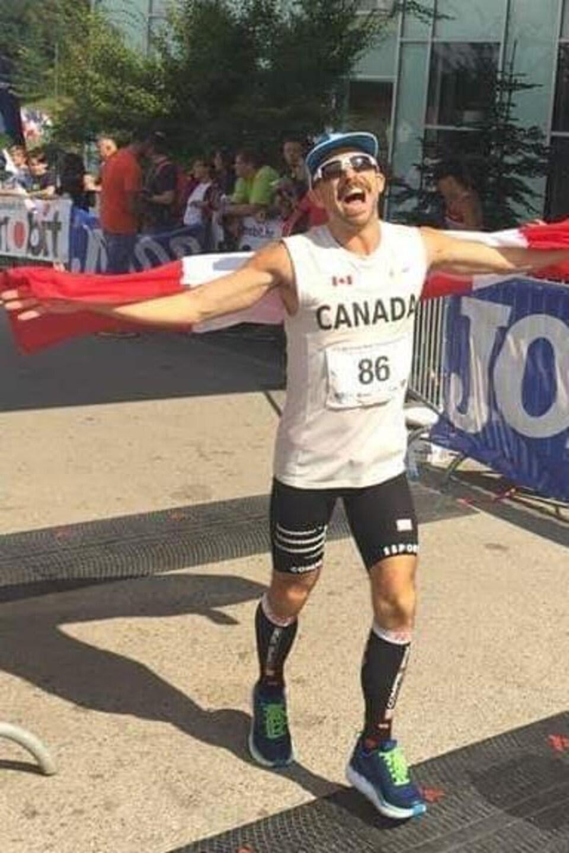Un coureur vêtu de blanc franchi la ligne d'arrivée du Championnat mondial de 100 km sur route en Croatie en 2018 avec un drapeau canadien dans les mains.