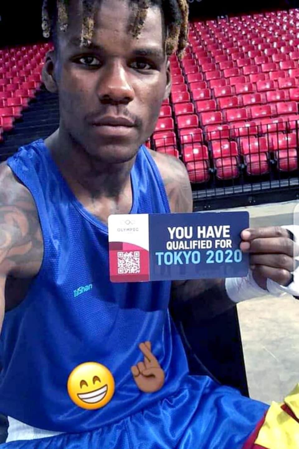 Il montre un morceau de carton sur lequel il est écrit, en anglais : « Vous vous êtes qualifié pour Tokyo 2020. »