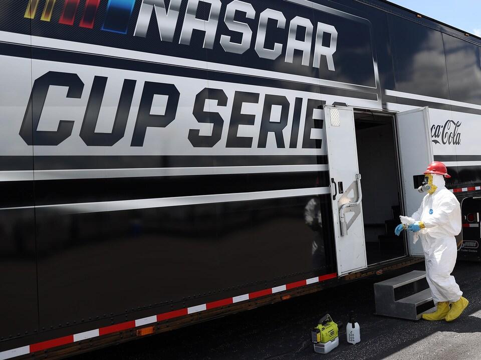 Un homme effectue un contrôle sanitaire à l'entrée du circuit avant une course NASCAR.