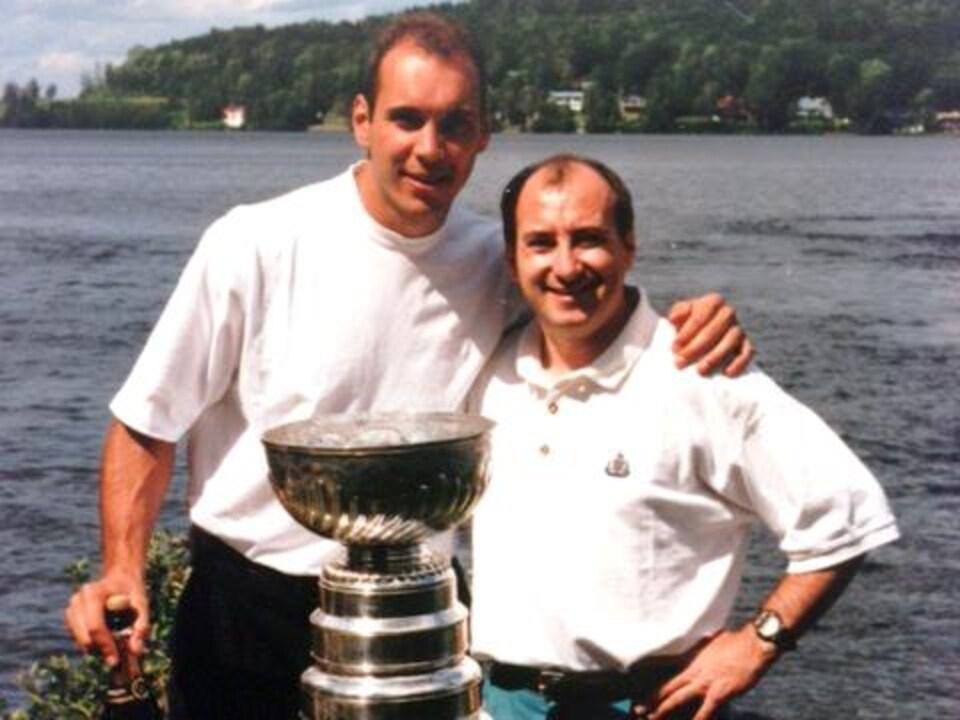 Sylvain Lefebvre et Jacques Lavergne posent derrière la coupe Stanley, devant un lac.