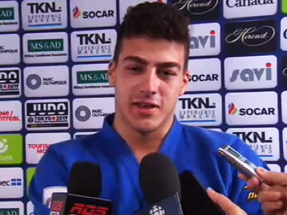 Vêtu de son judogi, il répond aux questions des journalistes.