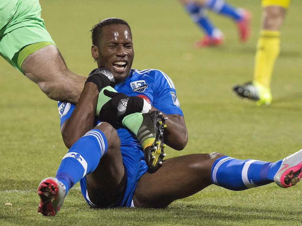 Didier Drogba agrippe la jambe du gardien.