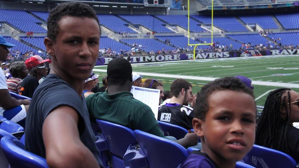 Les deux jeunes hommes, assis dans les gradins d'un stade, se retournent pour regarder la caméra.