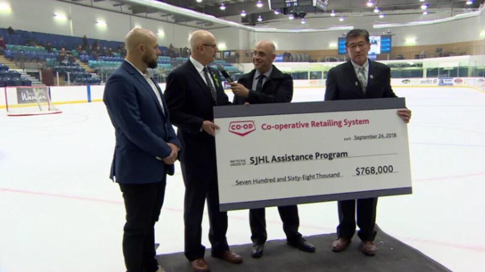 Bill Chow (à droite), photographié en september dernier, en train d'accepter un chèque de 768 000 $ pour le programme d'aide en santé mentale de sa ligue.