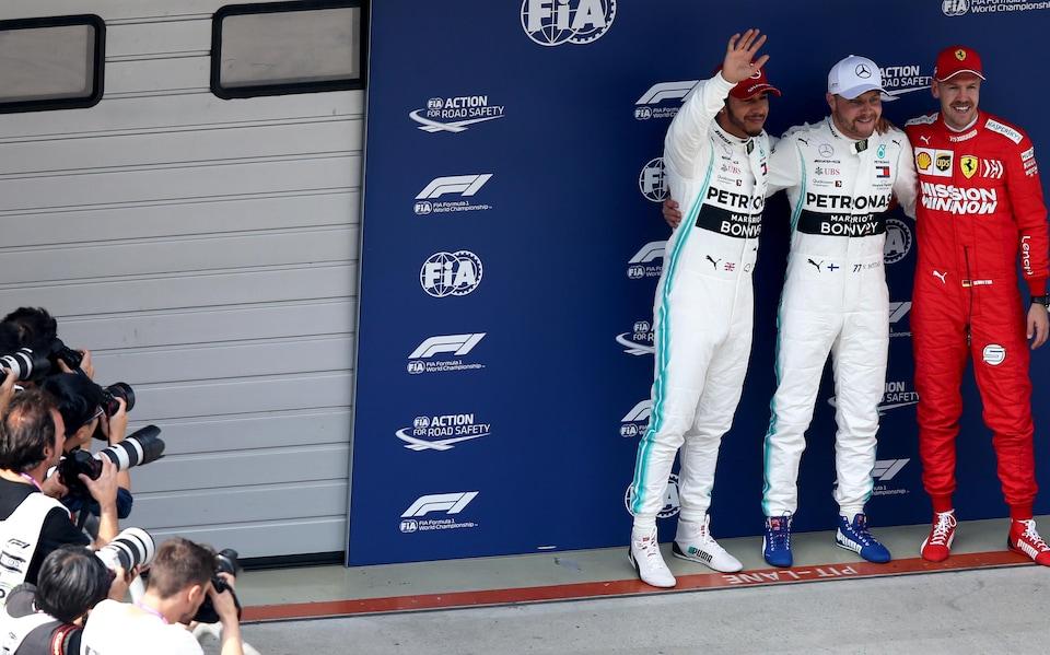 Valtteri Bottas salue la foule et les photographes entouré de Lewis Hamilton (à gauche) et de Sebastian Vettel après la séance de qualification du Grand Prix de Chine.