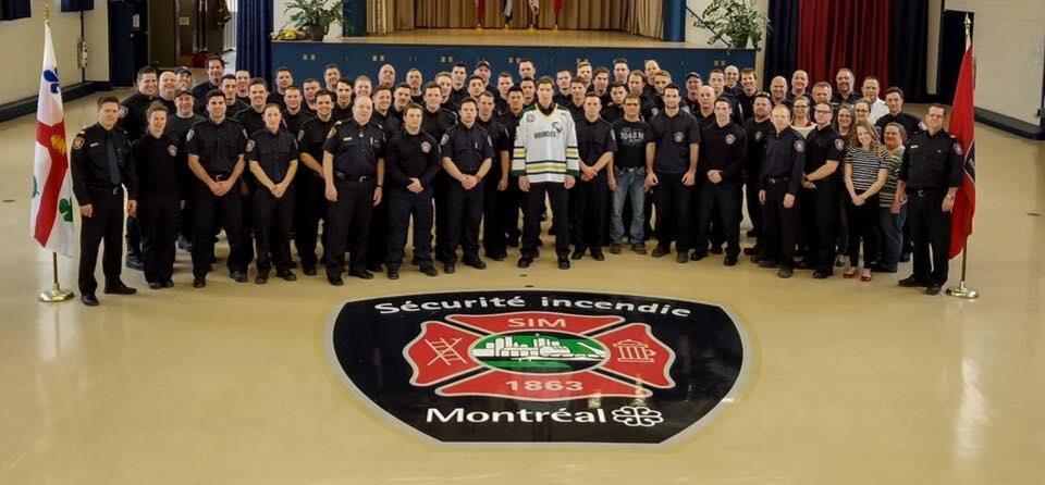 Vêtu de son chandail des Broncos, Jonathan Parisien pose avec 80 collègues du Service de sécurité incendie de Montréal.
