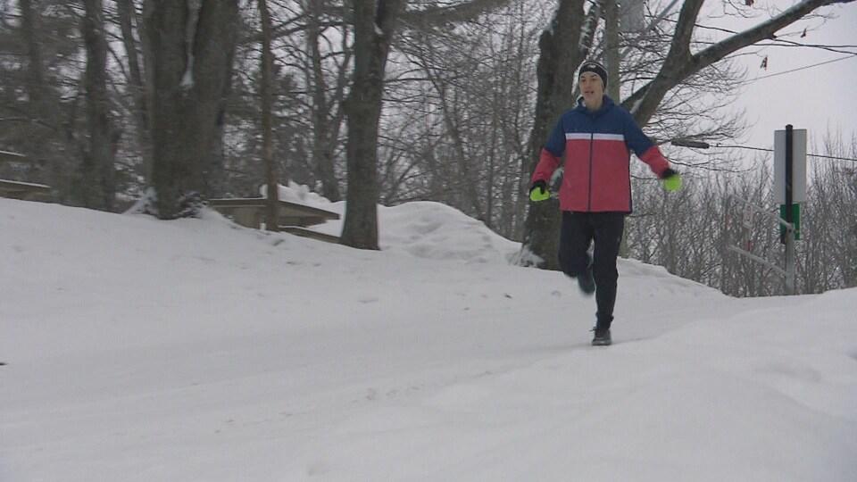 Geneviève Lalonde court dans un parc, entouré d'arbre et de neige.