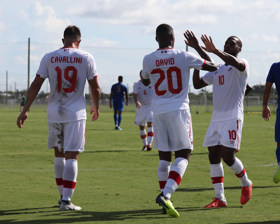 Jonathan David est félicité par ses coéquipiers après son premier but dans l'uniforme du Canada.