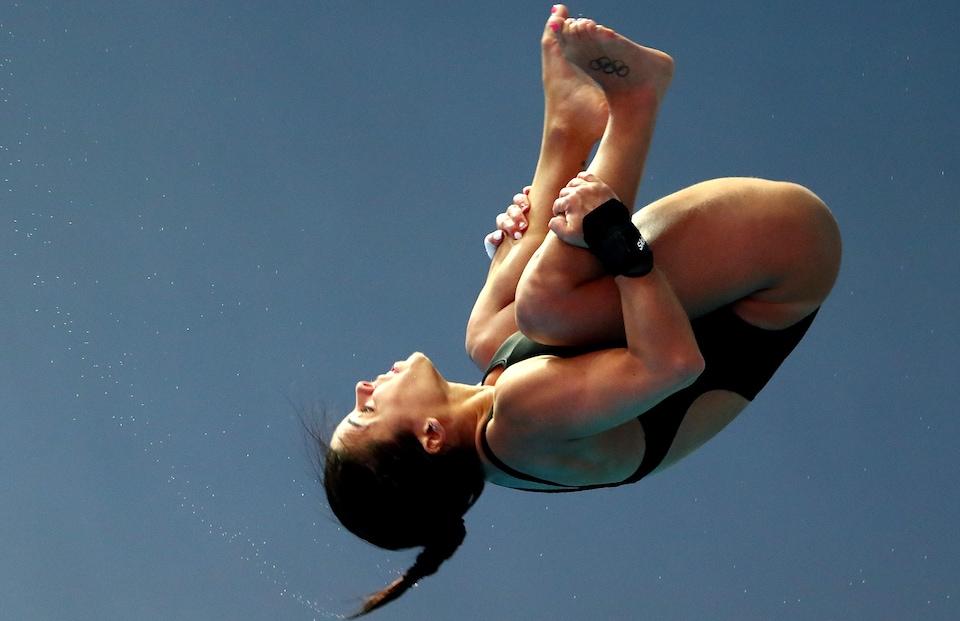 Elle effectue un plongeon en position groupée.