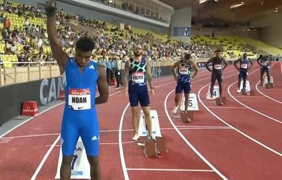 Noah Lyles lève son poing droit ganté avant son 200 m à Monaco en 2020.