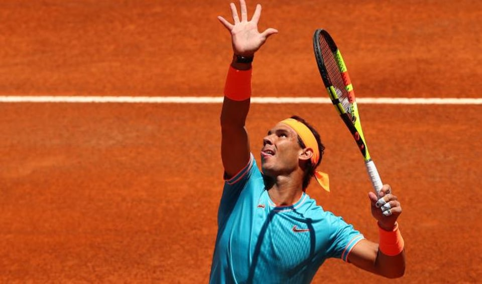 Rafael Nadal tire la langue en servant lors d'un match à Rome.