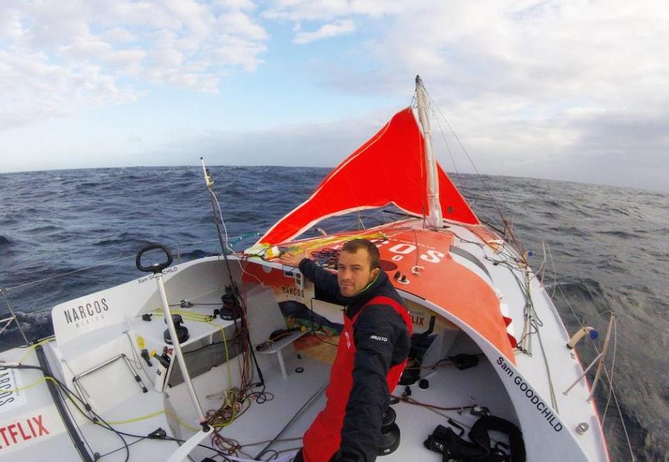 Le skipper Sam Goodchild dans son bateau Narcos Mexico. On voit le mât cassé à l'avant.