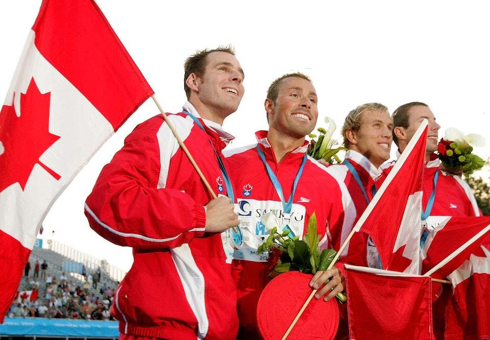 L'équipe canadienne avec des drapeaux, sourit pour les caméras