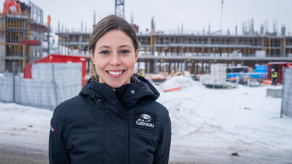 Maude Marquis-Bissonnette, en hiver, devant un édifice en construction.