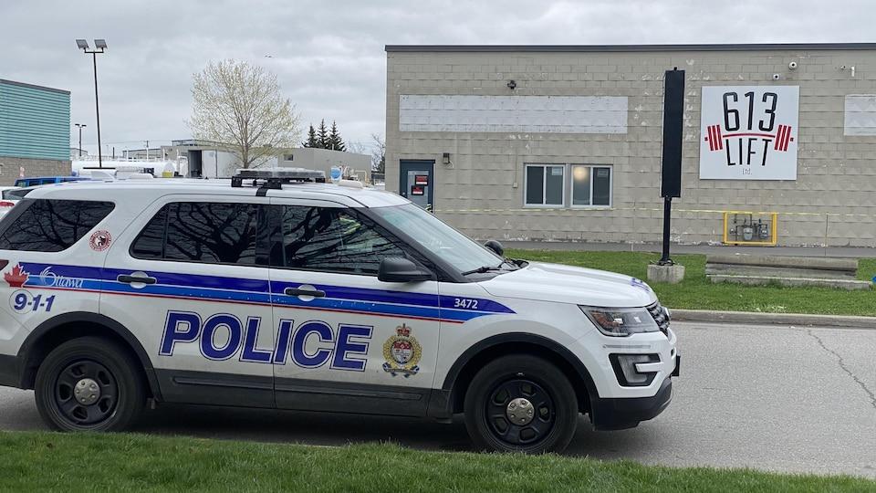 Une voiture de la police d'Ottawa devant un édifice.