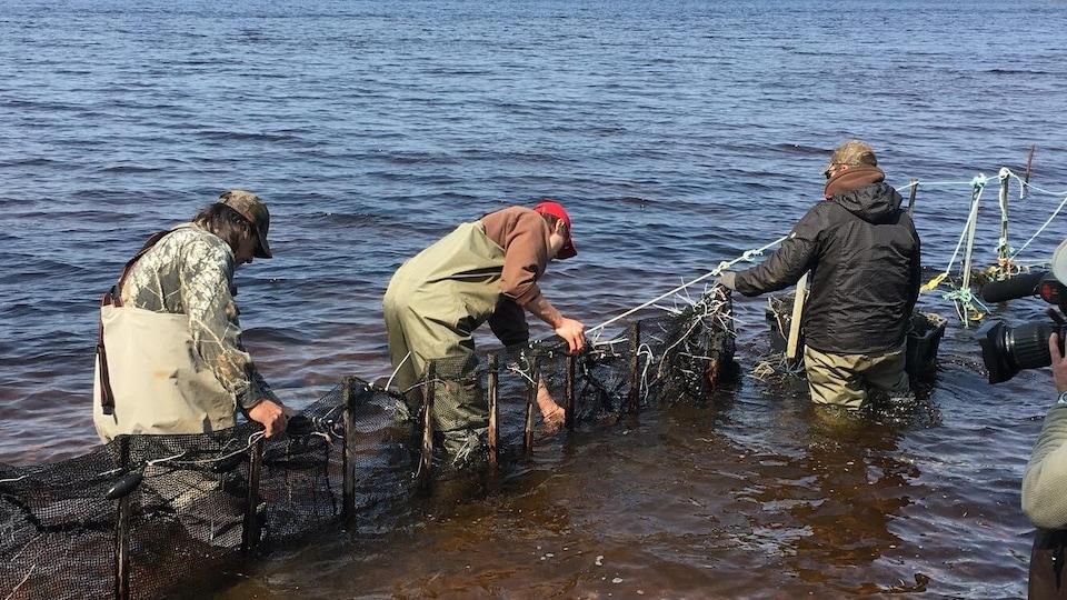 Trois hommes qui travaillent sur un barrage dans un lac.