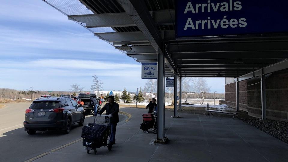 Des voyageurs poussent des bagages à la sortie de l'aéroport.