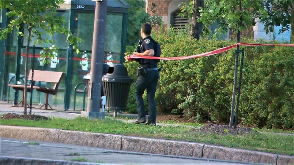Un policier attache un ruban sur un arbre et près d'un abribus