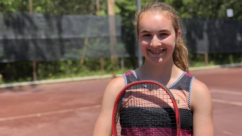 Ariane Souligny pose pour une photo avec sa raquette de tennis.