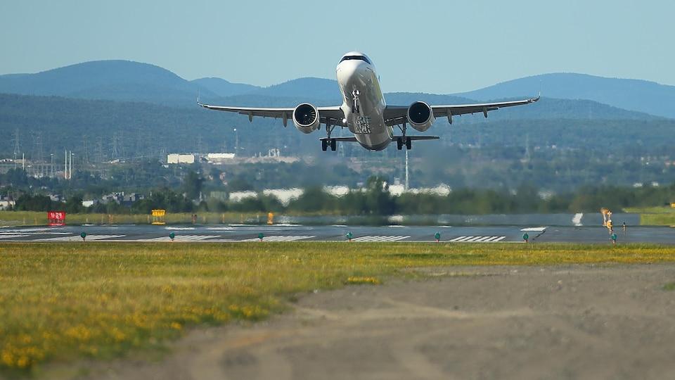 Un avion décolle de la piste d'un aéroport.