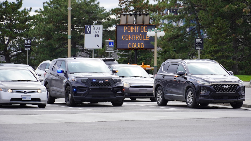 Des voitures alignées avec un panneau indiquant « point de contrôle COVID».